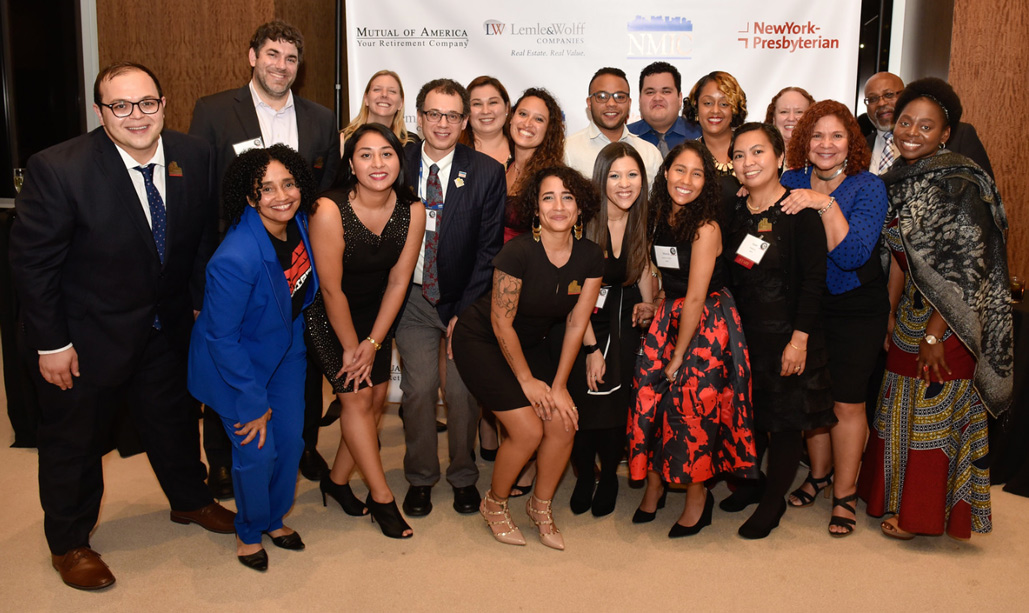 Members of NMIC's team pose in front of a backdrop of sponsor logos at a NMIC benefit