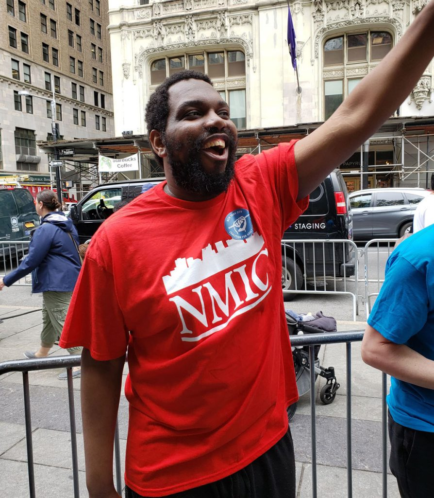 A dark-skinned man stands in a red shirt with a white NMIC logo on it holding his arm up and smilingly shouting