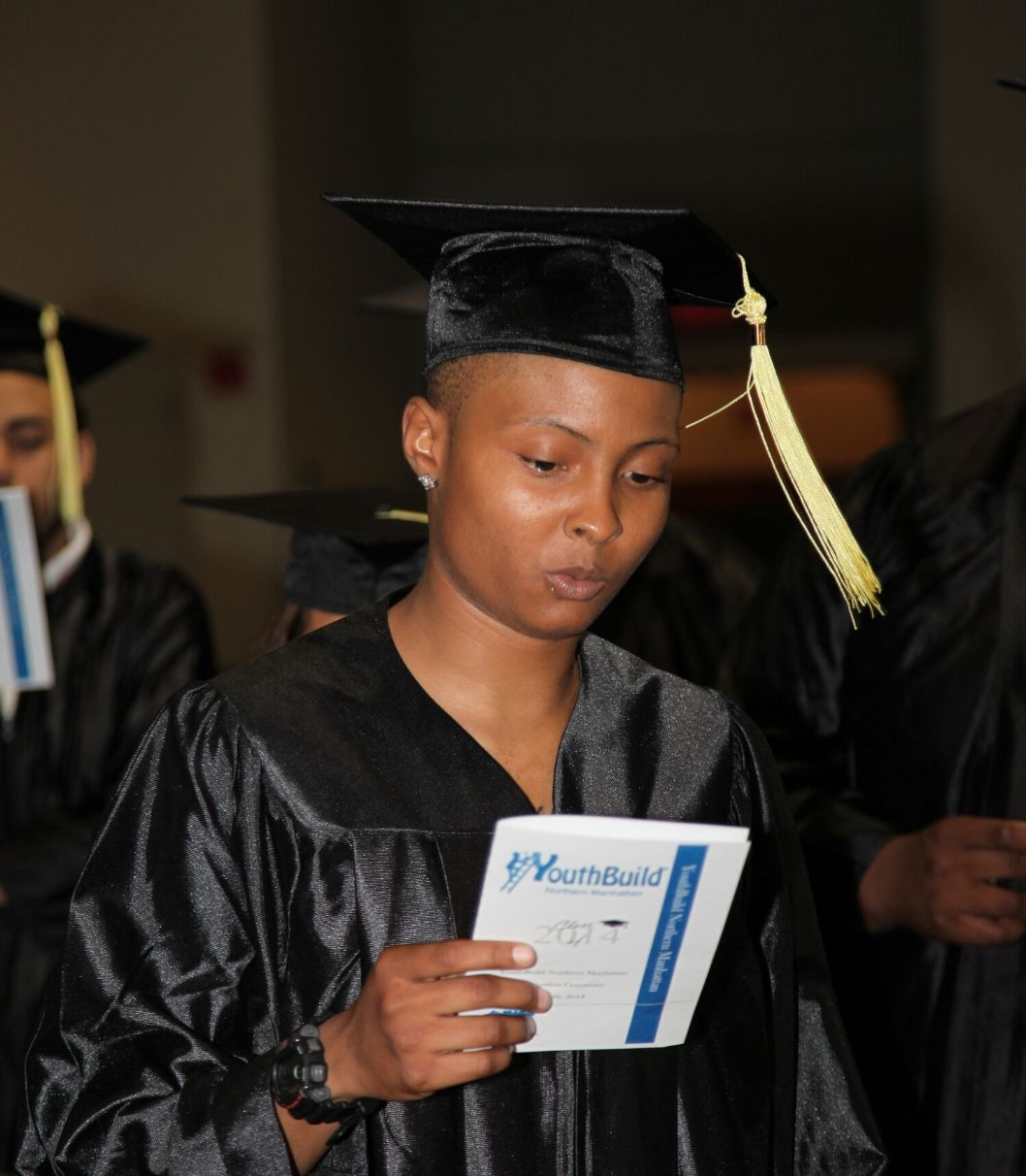 A young Black person in a Black cap and gown with gold tassels reads a white and blue program