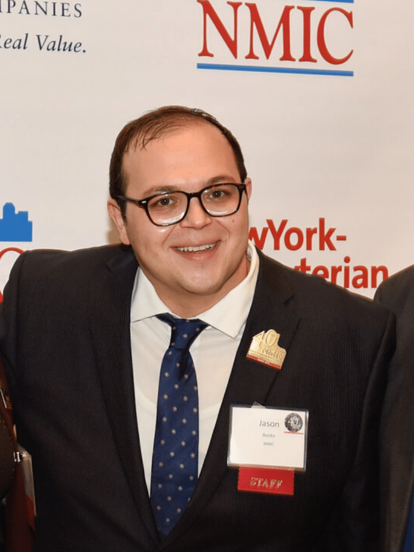 A photo of NMIC staff member Jason Bocko, a young white man, with short dark hair, dark-rimmed glasses smiles at the camera. He is wearing a dark suit, a white button-down shirt and a dark blue tie with light colored spots