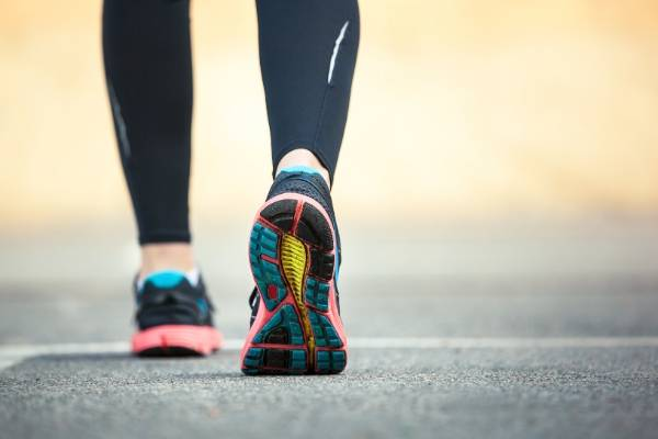 A photo from ground level of a persons calves in black workout leggings and colourful running shoes