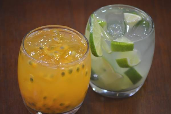 A photo of two beverages with ice in small glasses: a yellow drink with passionfruit seeds, and a clear drink with lime wedges