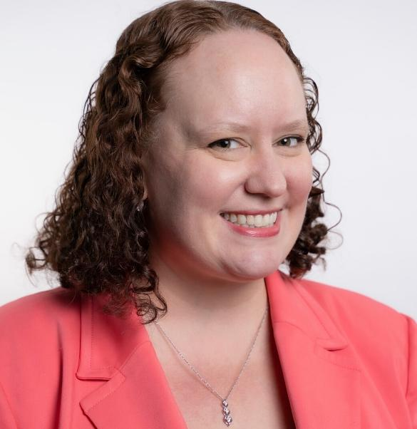 A headshot of Sara Chapman, NMIC's Director of Education & Career Services. She is a white woman with reddish brown curly hair. She smiles at the camera and is wearing a coral blazer