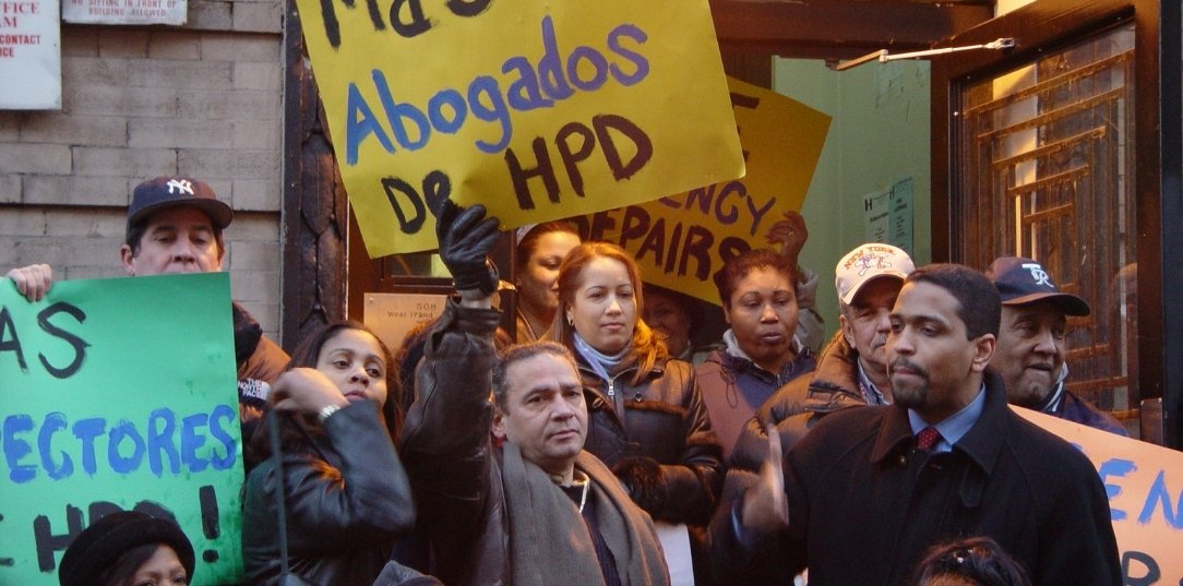 A group of people stand in a doorway holding signs to protest for tenant's rights