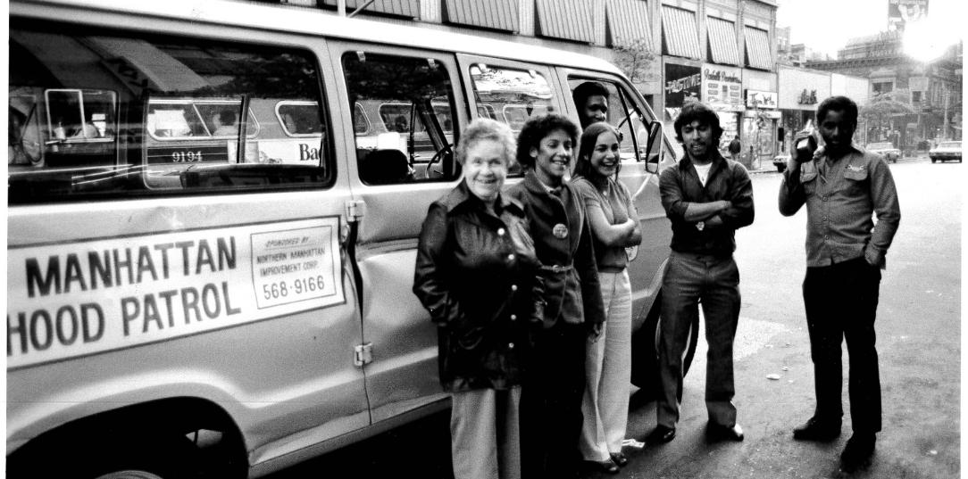 A Black and white photo from the 1980's of members of NMIC's neighborhood patrol pose in front of their van.