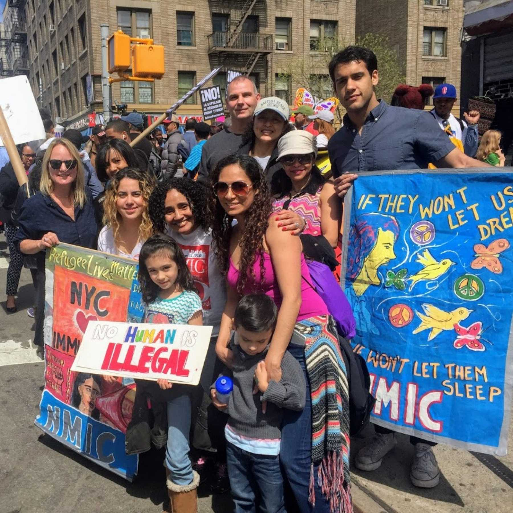 """Members of the NMIC team and community at an immigration protest. A man holds a sign that reads """"if they won't let us dream, we don't let them sleep NMIC"""", a child holds a sign that reads """"No Human is illegal"""", two women hold a sign that reads """"Refugee lives matter, NYC hearts Immigrants"""""""