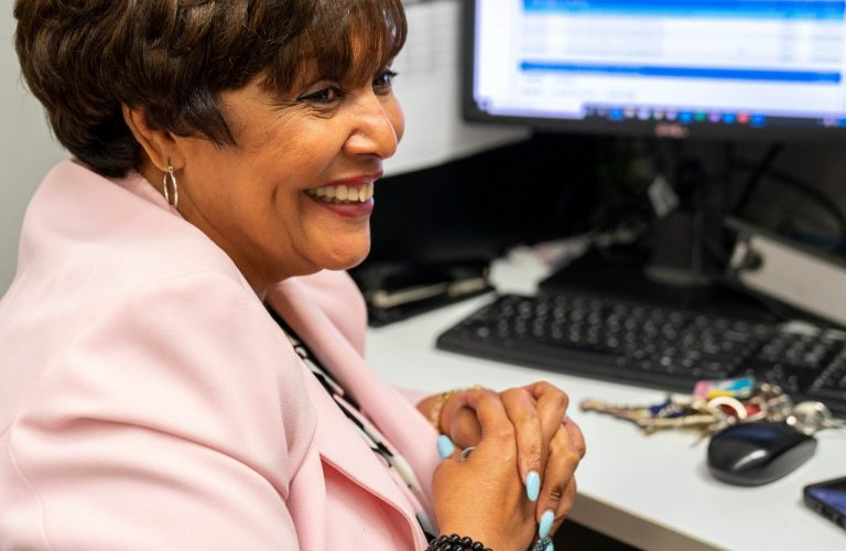 A brown-skinned older woman with short brown hair looks off-camera smilingly, she wears a light pink blazer, and holds her hands in front of her chest, her nails nicely manicured in light blue nail polish